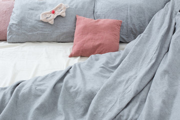 bed with gray linens and sleep mask