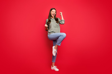 Full length photo of pretty funny lady yelling loud raising fists celebrating sports game match victory rejoicing wear casual grey green shirt jeans isolated red color background