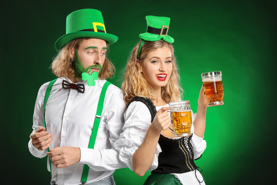 Young couple with beer on color background. St. Patrick's Day celebration