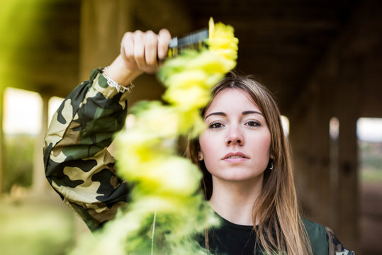 Brown hair girl holds a smoke bomb that throws yellow smoke around. Young girl wears an urban style, military jacket and piercing.