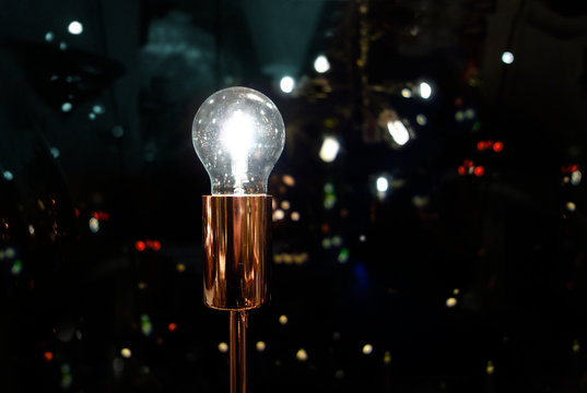 Sparkling Light bulb with night time modern urban background, symbolizing bright ideas in modern urban pulse of life