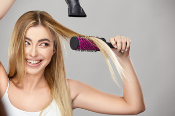 pretty blond uses hair dryer for her healthy long hair and smiling