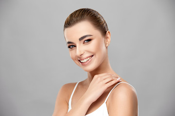elegant lady with perfect skin and light make-up smiling to camera and touching her shoulder
