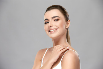 cute girl with nude mua smiling to camera in grey background