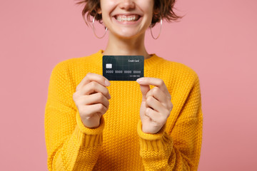 Cropped image of smiling young brunette woman girl in yellow sweater posing isolated on pastel pink wall background studio portait. People lifestyle concept. Mock up copy space. Hold credit bank card.