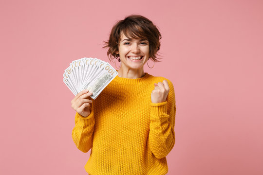 Joyful young brunette woman in yellow sweater posing isolated on pastel pink background. People lifestyle concept. Mock up copy space. Hold fan of cash money in dollar banknotes, doing winner gesture.