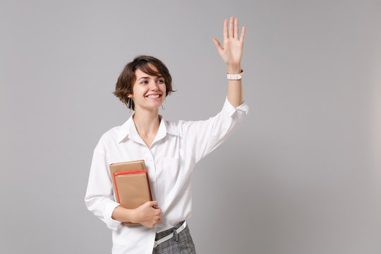 Joyful business woman in white shirt isolated on grey background. Achievement career wealth business concept. Mock up copy space. Hold books, notebooks, waving greeting with hand as notices someone.