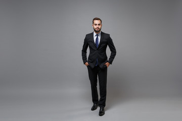 Attractive young bearded business man in classic black suit shirt tie posing isolated on grey wall...