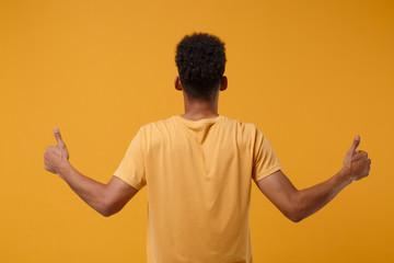 Back rear view of young african american guy in casual t-shirt posing isolated on yellow orange...