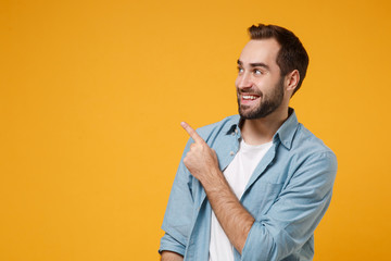 Smiling young bearded man in casual blue shirt posing isolated on yellow orange background studio portrait. People sincere emotions lifestyle concept. Mock up copy space. Pointing index finger up.