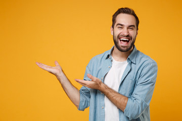 Laughing young bearded man in casual blue shirt posing isolated on yellow orange wall background,...