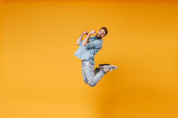 Happy young bearded man in casual blue shirt posing isolated on yellow orange background, studio portrait. People sincere emotions lifestyle concept. Mock up copy space. Jumping doing winner gesture.