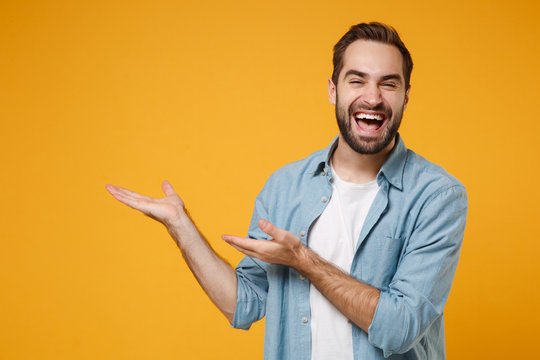 Laughing young bearded man in casual blue shirt posing isolated on yellow orange wall background, studio portrait. People sincere emotions lifestyle concept. Mock up copy space. Pointing hands aside.