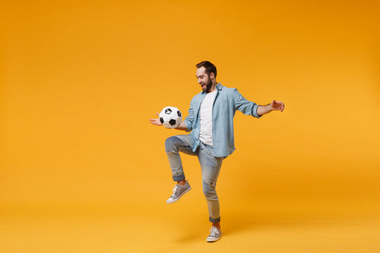 Cheerful young man in casual blue shirt posing isolated on yellow orange wall background, studio portrait. People emotions lifestyle concept. Mock up copy space. Juggling bouncing soccer ball on knee.