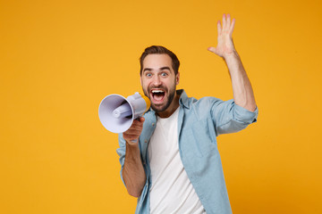 Excited young man in casual blue shirt posing isolated on yellow orange background, studio portrait. People sincere emotions lifestyle concept. Mock up copy space. Scream in megaphone, rising hand.