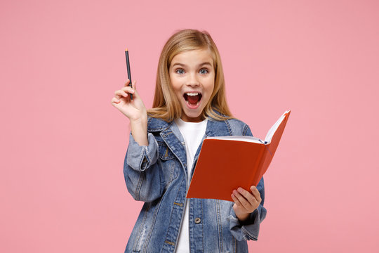 Excited little blonde kid girl 12-13 years old in denim jacket isolated on pastel pink background children studio portrait. Childhood lifestyle concept. Mock up copy space. Holding notebook, pencil.