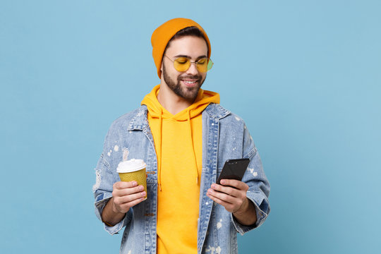 Smiling young hipster guy in fashion jeans denim clothes posing isolated on pastel blue background. People lifestyle concept. Mock up copy space. Using mobile phone, hold paper cup of coffee or tea.