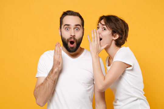 Shocked couple friends bearded guy girl in white t-shirts posing isolated on yellow orange background. People lifestyle concept. Mock up copy space. Whispers gossip and tells secret with hand gesture.