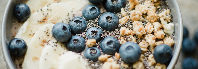 Healthy breakfast berry smoothie bowl topped with banana, granola, Blueberries and chia seeds with copy space