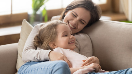 Smiling mother and adorable little daughter relaxing together on couch