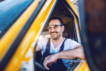 Smiling handsome unshaven worker driving vehicle on construction site.