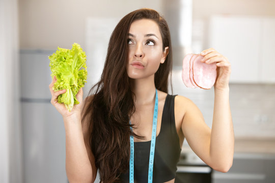 young fit woman with centimeter round her neck holding fresh salad in one hand and slice of ham in another looks doubtful,nutrition and dietology