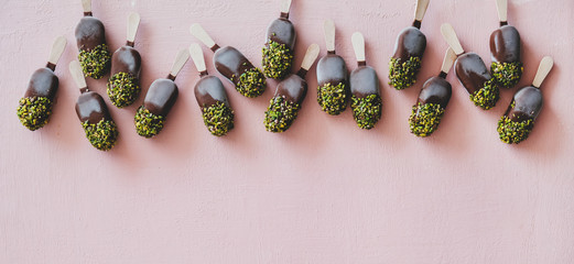 Ice cream popsicle pattern. Flat-lay of chocolate glazed ice cream pops with pistachio icing over...