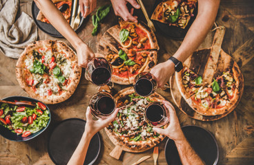 Family or friends having pizza party dinner. Flat-lay of people clinking glasses with red wine over rustic wooden table with various kinds of Italian pizza, top view. Fast food lunch, celebration