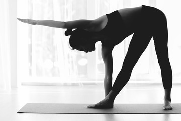 Sporty woman practicing yoga, doing triangle asana