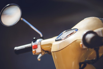Scooter The steering wheel of a vintage beige moped with a dashboard and a round rearview mirror is illuminated with bright light.