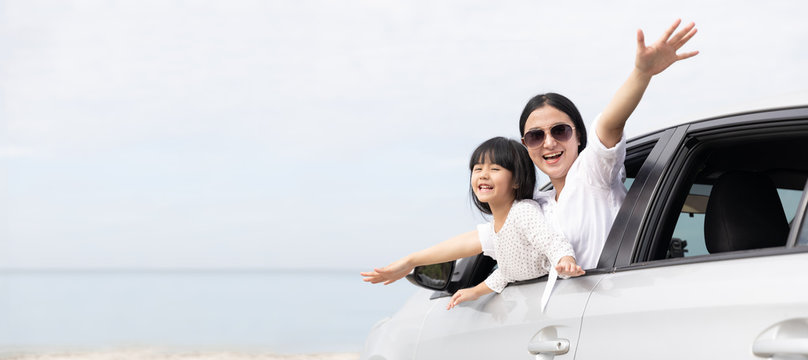 Happy Asian Family On Summer Vacation Mother and daughter Open arms playing plane flying together in car on the beach. Holiday and Car Travel concept. panoramic web banner with copy space