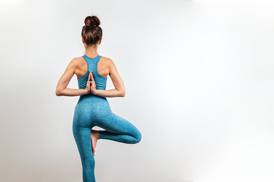 Yoga and sports concept. A young Caucasian woman is engaged in yoga. White background in the background. The view from the back. Copy space