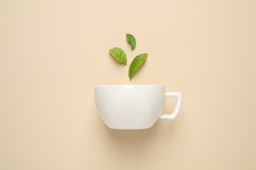 Foto op Textielframe Thee Fresh tea leaves and cup on beige background, top view