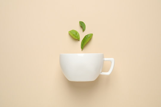 Fresh tea leaves and cup on beige background, top view