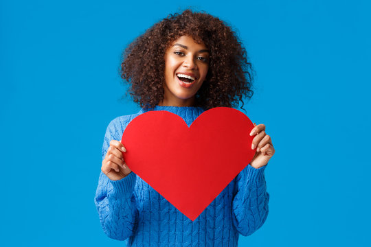 Lovely and cute african-american pretty woman with afro haircut, holding valentines day card, big heart and smiling, express love and affection, showing true feelings, search soulmate