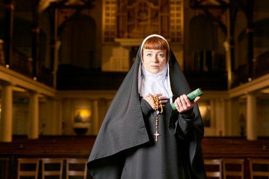 nun in church with rosary and bible