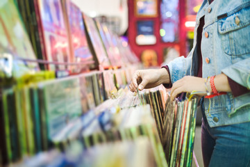 Fotorolgordijn Muziekwinkel Young Woman Choosing Vintage Vinyl LP In Records Shop