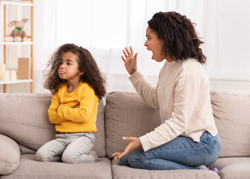 Angry Mother Shouting At Daughter Sitting On Couch At Home