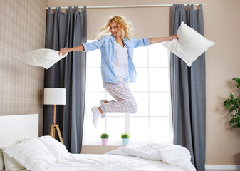 happy young woman laughing and jumping on the bed in   morning at home