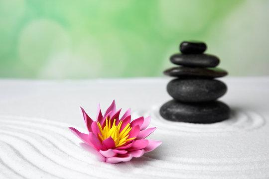 Zen garden. Beautiful lotus flower and stones on white sand