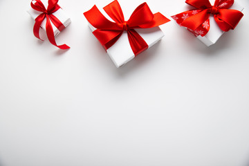 White gifts with red ribbon, present on white background top view. Happy Holidays. Valentine's day....