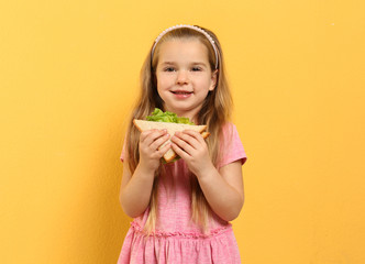 Photo sur Aluminium Snack Cute little girl with tasty sandwich on yellow background