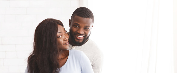 Young joyful married couple posing over white background