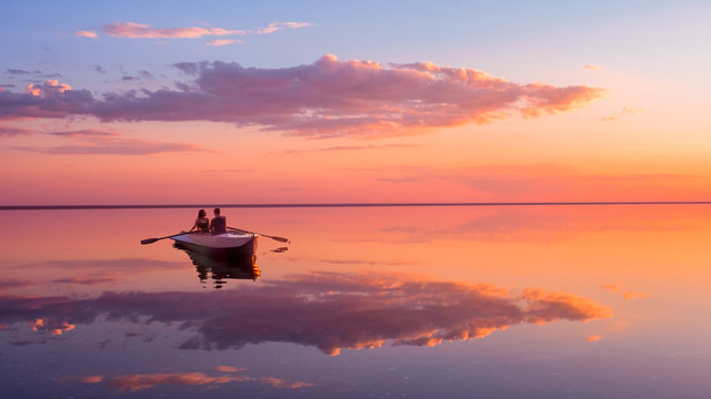 A couple in love look at beautiful sunset in a rowing boat on the lake. Pink sky and vanilla clouds. Romantic scene - lovers ride a boat in nature during sunset. Amazing landscape with people