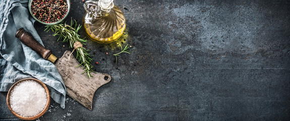 Organic food concept with olive oil salt peppet rosemary and kitchen utensil - butcher knife