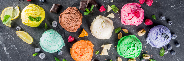 Colorful pastel ice cream with waffle cones and various flavor ingredients, black marble background, copy space top view