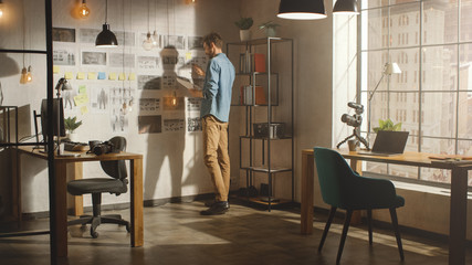Young Creative Man Stands Next to the Wall with Organized Mood Board in His Cool Loft Office. He...