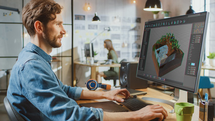 Beautiful Male Working in an Urbanistic Programm Creating 3 visualisation on His PC with Big Display. He Works in a Cool Office Loft. Other Female Creative Colleague Works in the Background. Wall mural
