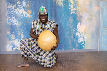 Handsome African man with traditional clothes and musical instruments Wall mural