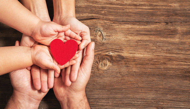 family hands holding red heart on wooden background. Donation, charity, health concept.